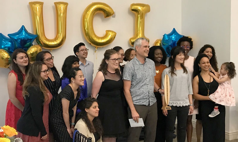 Ph.D. Public Health students recognize outgoing Director of Ph.D. in Public Health, Dr. Scott Bartell with an award of a mini surf board at the 2019 Graduate Honors and Awards Ceremony